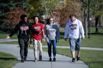 three male students and one female student walking on campus