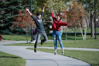 Two students jumping in the air on a sidewalk
