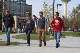 Four young students, 3 males and 1 female, walking on the sidewalk in front of the main entrance at the Willmar campus.