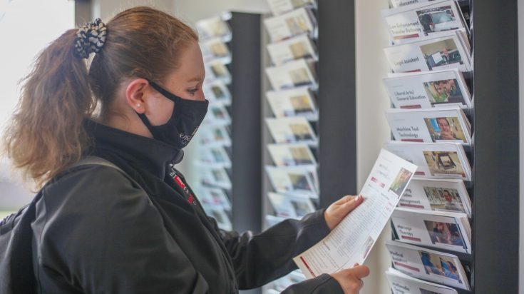 Photo of a student looking an information sheet